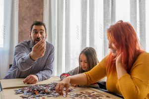 Family doing puzzle in the living room at home.